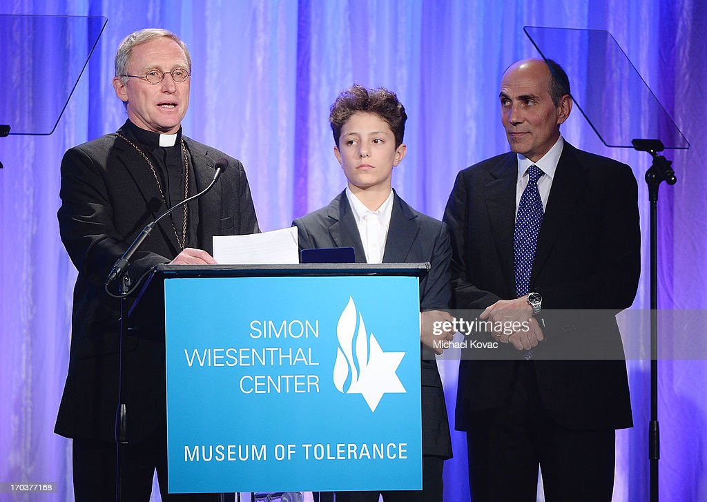 The Medal of Valor is accepted by Father Norbert Hofmann (L) accompanied by Lamberto Piperno (R) and his son Ariel (R) at the Simon Wiesenthal Center National Tribute Dinner at Regent Beverly Wilshire Hotel on June 11, 2013 in Beverly Hills, California.