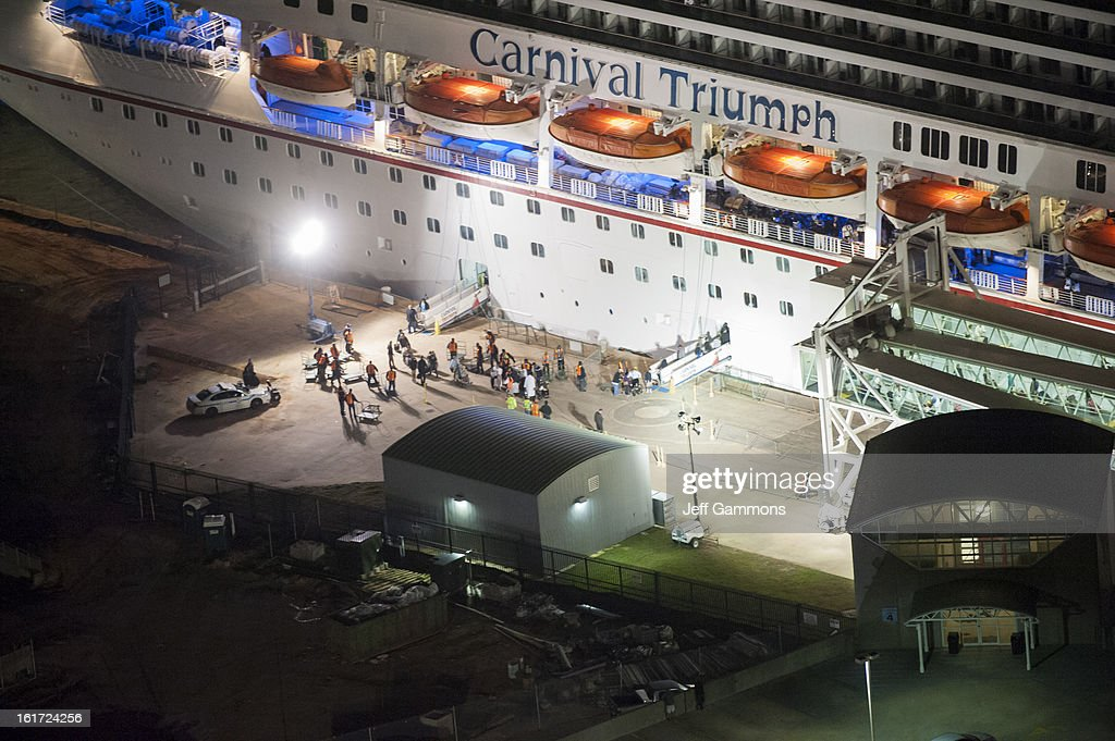 The media await the final unloading from the crippled cruise liner Carnival Triumph February 14, 2013 in Mobile, Alabama. An engine fire on February 10 left the ship and its 4,000 passengers without power and with scarce food. While people onboard reported toilets that wouldn't work, the ship was restocked with food during the days it was being towed through the Gulf of Mexico. According to reports, a few dozen people awaited the ship's arrival in Mobile, covered live by cable news network CNN.