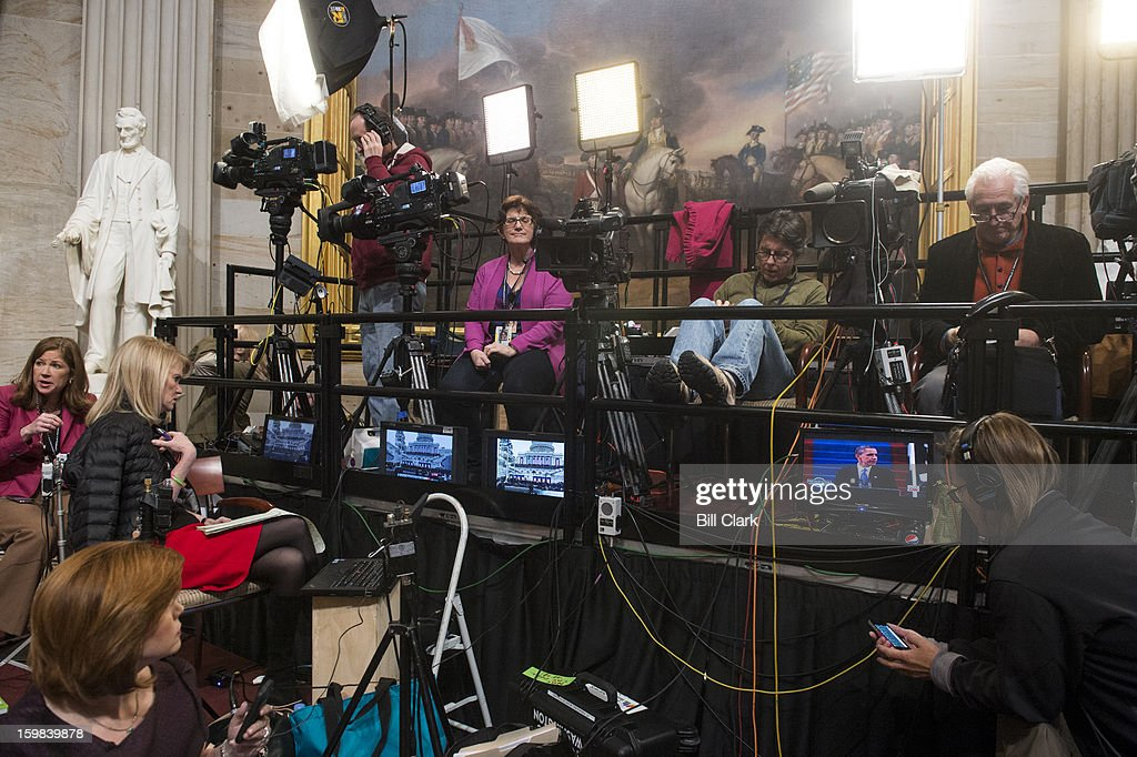 The media camped out in the Rotunda watches President Barack Obama's inauguration speech on monitors as they wait for the President to arrive for the luncheon in Statuary Hall on Monday morning, Jan. 21, 2013.