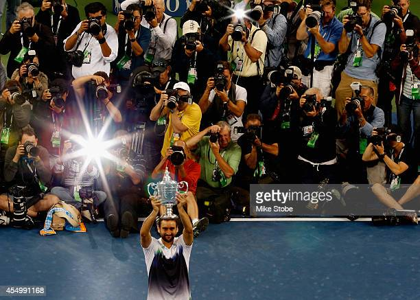 The media photograph Marin Cilic of Croatia as he celebrates with the trophy after defeating Kei Nishikori of Japan to win the men's singles final...