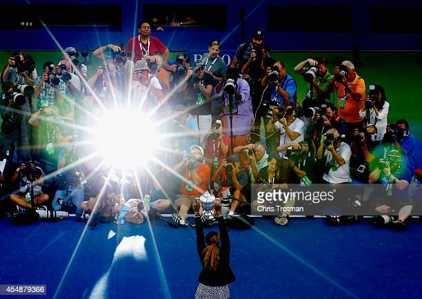 The media photograph Serena Williams of the United States as she celebrates with the trophy after defeating Caroline Wozniacki of Denmark to win...