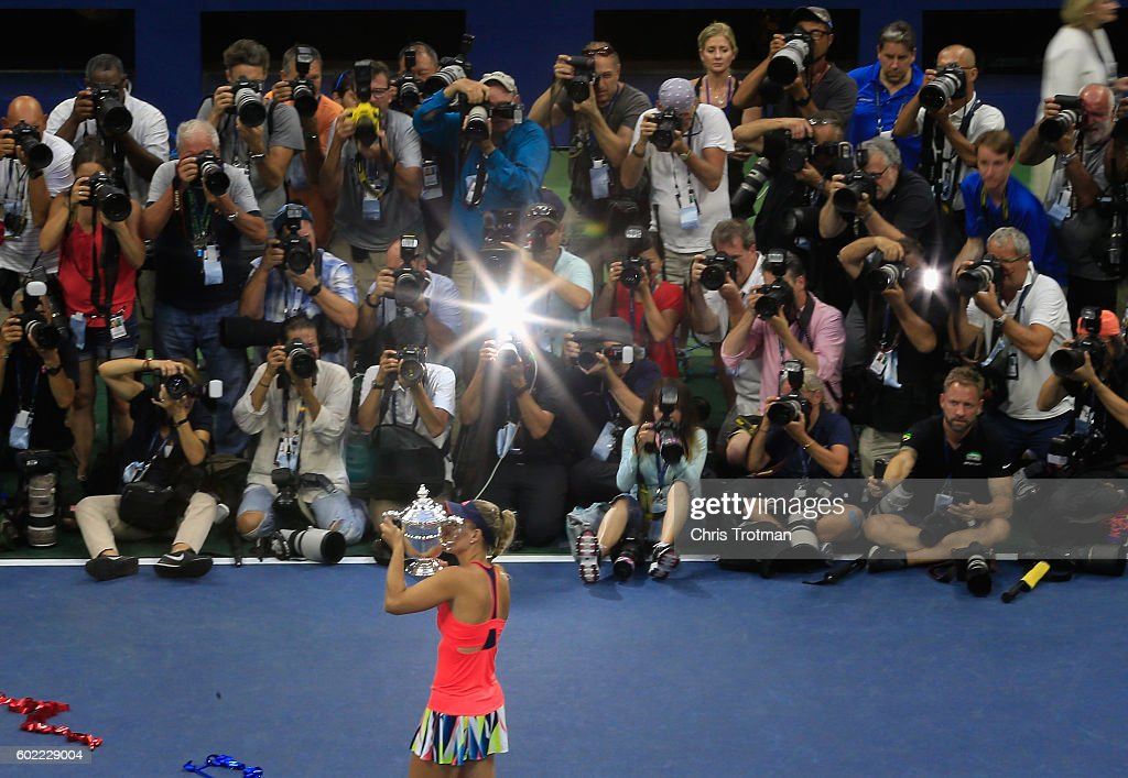 The media photographs Angelique Kerber of Germany as she celebrates with the trophy after winning (6-3) (4-6) (6-4) against Karolina Pliskova of the Czech Republic during their Women's Singles Final Match on Day Thirteen of the 2016 US Open at the USTA Billie Jean King National Tennis Center on September 10, 2016 in the Queens borough of New York City.