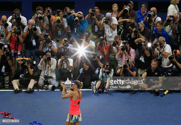The media photographs Angelique Kerber of Germany as she celebrates with the trophy after winning against Karolina Pliskova of the Czech Republic...