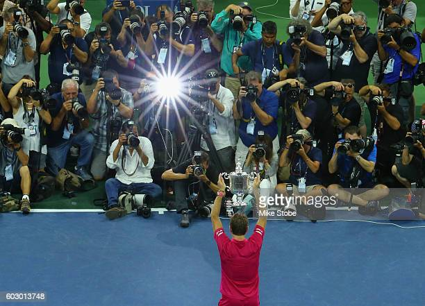 The media photographs Stan Wawrinka of Switzerland celebrating with the trophy after winning 67 64 75 63 against Novak Djokovic of Serbia during...