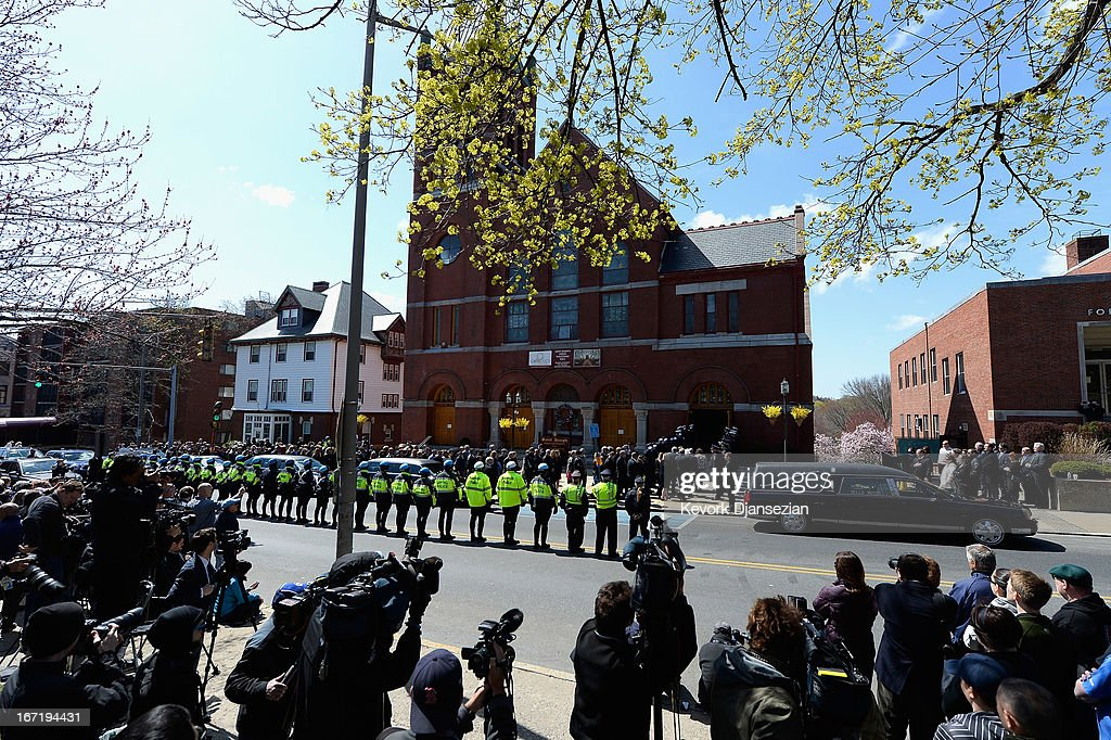 The media stand across the street as Medford Police line the street while the hearse arrives at St. Joseph Catholic Church for the funeral of Krystle Campbell, a victim of the Boston Marathon bombing, on April 22, 2013 in Medford, Massachusetts. A manhunt ended for Dzhokhar A. Tsarnaev, 19, a suspect in the Boston Marathon bombing after he was apprehended on a boat parked on a residential property in Watertown, Massachusetts. His brother Tamerlan Tsarnaev, 26, the other suspect, was shot and killed after a car chase and shootout with police. The bombing, on April 15 at the finish line of the marathon, killed three people and wounded at least 170.