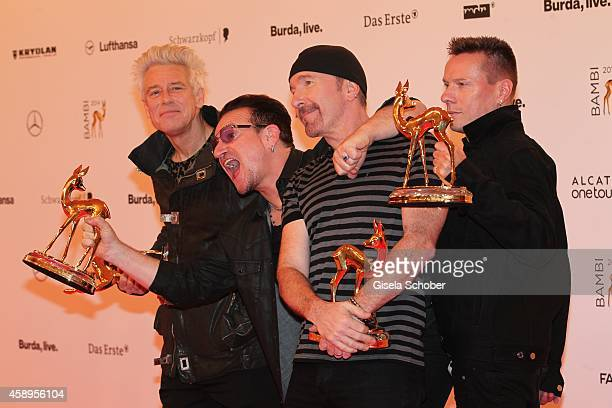 The members of the band U2 Adam Clayton Bono The Edge and Larry Mullen junior pose with their award at the winners board during the Bambi Awards 2014...