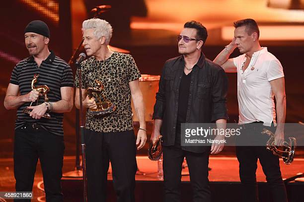 The members of the band U2 The Edge Adam Clayton Bono and Larry Mullen junior are seen on stage during the Bambi Awards 2014 show on November 13 2014...