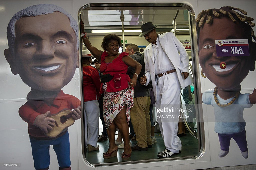 The members of Vila Isabel Samba school perform on the special Samba train at Central station in Rio de Janeiro on December 7, 2013. Samba trains are offering direct 20-minute ride to the Oswaldo Cruz station where a 6-day-long event 'Trem do Samba' is taking place on the outskirts of Rio de Janeiro.