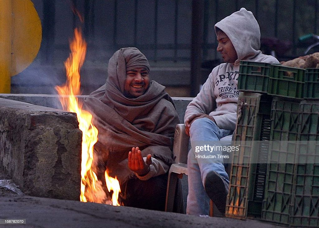 The men feel comfortable near the fire the cold and foggy weather at Myur Vihar, on December 28, 2012 in New Delhi, India. While the maximum temperature was recorded at 19 deg C, up from yesterday's temperature by 2.4 degrees, the minimum temperature today dipped to 6.3 deg C, a degree below the normal.
