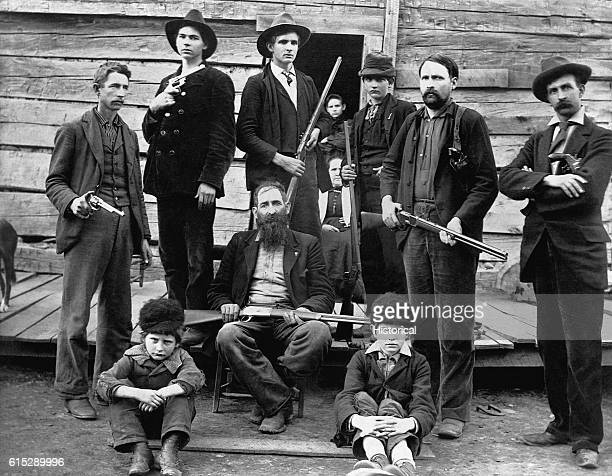 The men of the Hatfield family pose outside their cabin holding shotguns and pistols The West Virginia Hatfields fought a legendary feud with the...