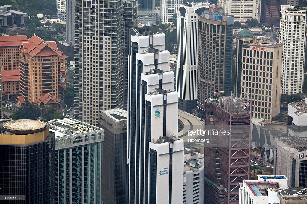 The Menara Standard Chartered building, center, stands in the central business district in Kuala Lumpur, Malaysia, on Wednesday, Jan. 16, 2013. While many developed countries have faltered, Malaysia's gross domestic product growth has exceeded 5 percent for five quarters with domestic demand countering a slowdown in exports. Photographer: Lam Yik Fei/Bloomberg via Getty Images