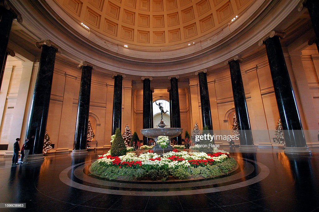 CONTENT] The Mercury fountain in the National Gallery of Art West building is surrounded by red and white flowers and lighted Christmas trees.