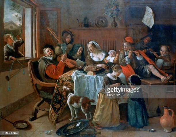 The Merry Family' Dutch interior showing a family making music round a table covered in a carpet and a cloth with the remains of a meal Even the dog...