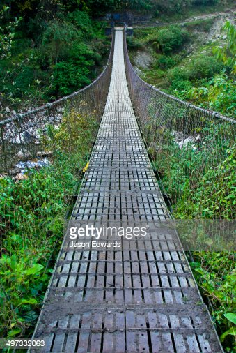 The metal planks of a suspension bridge cross between mountain valley walls in the Himalaya.