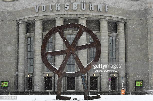 The metal sculpture of the RosaLuxemburgPlatz square is pictured in front of the main entrance of the Volksbuehne during snowfall in Berlin's central...