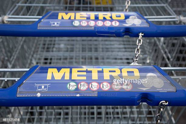 The Metro logo sits on the euro coin release of shopping carts inside a wholesale store operated by Metro AG in Cologne Germany on Wednesday Jan 7...