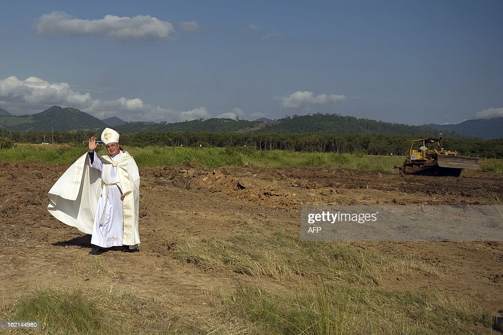 The Metropolitan Archbishop of Rio de Janeiro, Dom Orani Tempesta, blesses the place where the Pope is to celebrate mass during the July 27 and 28 visit and in the framework of the World Youth Day, in a farm in Guaratiba, western Rio de Janeiro, on February 19, 2013. According to official sources, about three million people are expected to attend the event. AFP PHOTO/VANDERLEI ALMEIDA