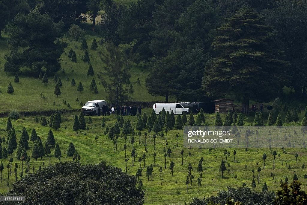 The Mexican police and forensic personnel work on August 22, 2013 at a park in the municipality of Tlalmanalco, some 30 km southeast of Mexico City, where at least 7 bodies were discovered in a mass grave. Mexican authorities dug up the muddy mass grave and were investigating Thursday if the remains belong to 12 young people whose kidnapping in May shocked the capital. Mexico City's top prosecutor, Rodolfo Rios, said the remains of seven people have been recovered since the search began in a park on Wednesday and that workers are still digging for more bodies. The victims were kidnapped from a downtown bar in broad daylight on a Sunday morning three months ago in a case that raised concerns about security in Mexico City, which has been relatively immune from the country's drug cartel violence.