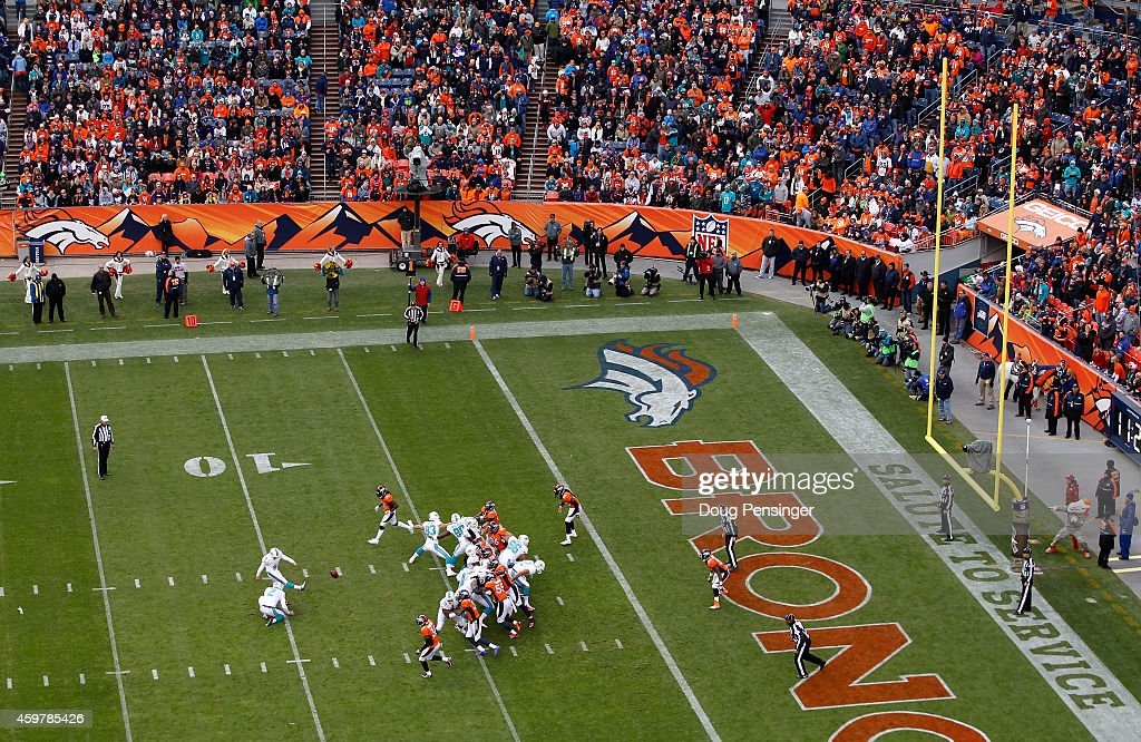 The Miami Dolphins kick an extra point against the Denver Broncos defense at Sports Authority Field at Mile High on November 23 2014 in Denver...