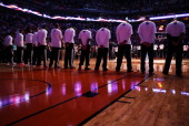 The Miami Heat stand attended for the National Anthem before the NBA game against the Phoenix Suns at US Airways Center on February 11 2014 in...