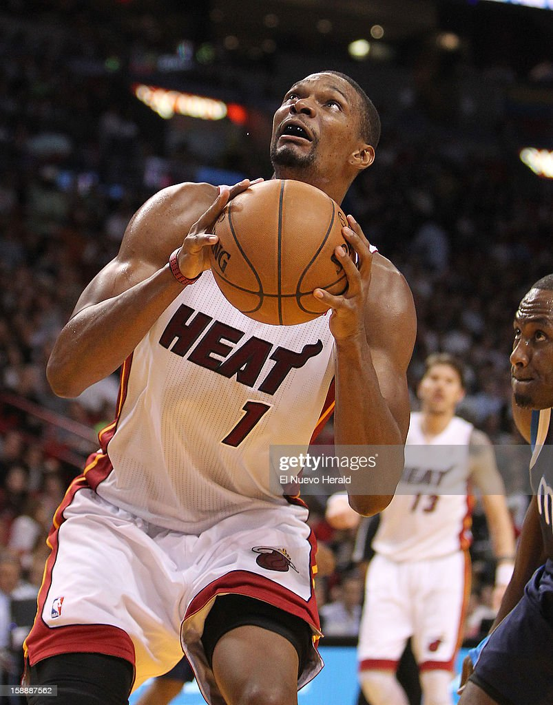 The Miami Heat's Chris Bosh goes to the basket against the Dallas Mavericks' Elton Brand, right, during the second quarter at the AmericanAirlines Arena in Miami, Florida, on Wednesday, January 2, 2013.