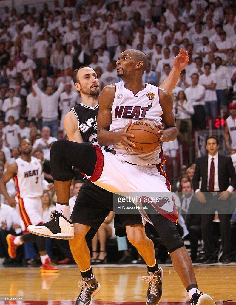 The Miami Heat's Chris Bosh grabs a rebound against the San Antonio Spurs' Manu Ginobili during overtime in Game 6 of the NBA Finals on Tuesday, June 18, 2013, at the AmericanAirlines Arena in Miami, Florida. Miami won, 103-100, in overtime to force a Game 7.