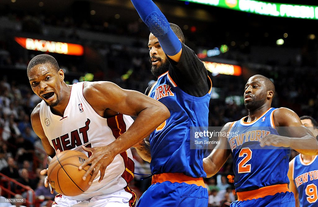 The Miami Heat's Chris Bosh, left, looks for room to work against the New York Knicks' Tyson Chandler and Raymond Felton (2) at AmericanAirlines Arena in Miami, Florida, on Tuesday, April 2, 2013.