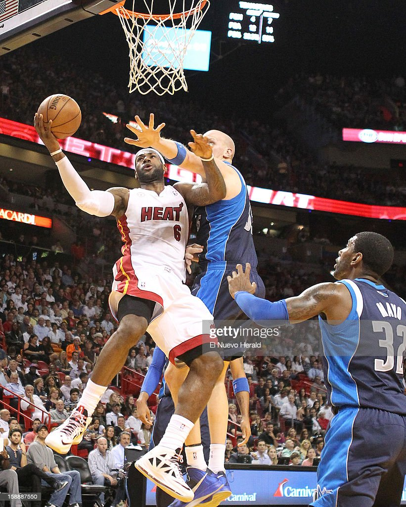The Miami Heat's LeBron James (6) goes to the basket against the Dallas Mavericks' Chris Kaman, left, and O.J. Mayo during the first quarter at the AmericanAirlines Arena in Miami, Florida, on Wednesday, January 2, 2013.