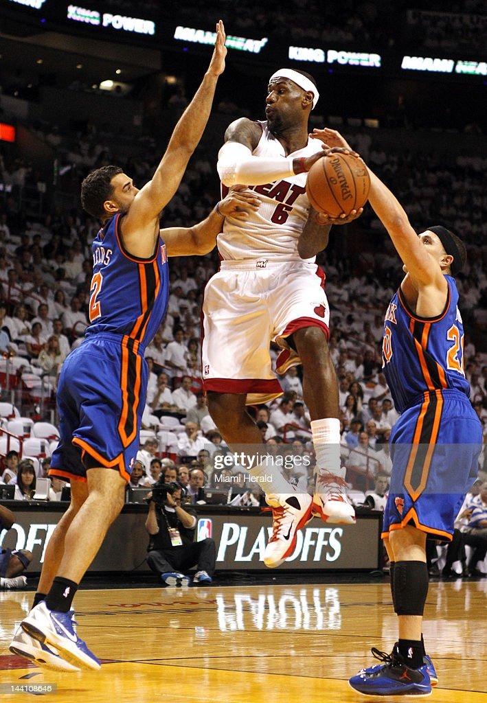 The Miami Heat's LeBron James leaps between the New York Knicks' Landry Fields, left, and Mike Bibby in the first quarter in Game 5 of the Eastern Conference first-round series at American Airlines Arena in Miami, Florida, on Wednesday, May 9, 2012.