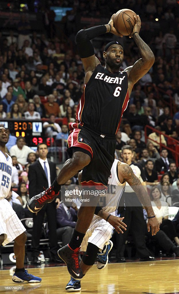 The Miami Heat's LeBron James leaps under the basket to pass the ball against the Orlando Magic late in the fourth quarter at the AmericanAirlines Arena in Miami, Florida, on Wednesday, March 6, 2013. Miami edged Orlando, 97-96.
