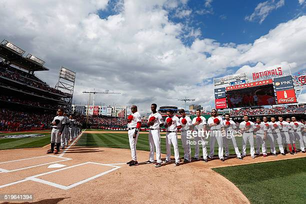 The Miami Marlins and Washington Nationals listen to the national anthem before the start of the Nationals home opener at Nationals Park on April 7...