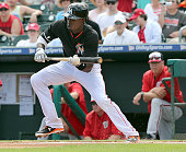 The Miami Marlins' Dee Gordon bunts for a single in the first inning against the Washington Nationals in Grapefruit League action on Tuesday March 10...
