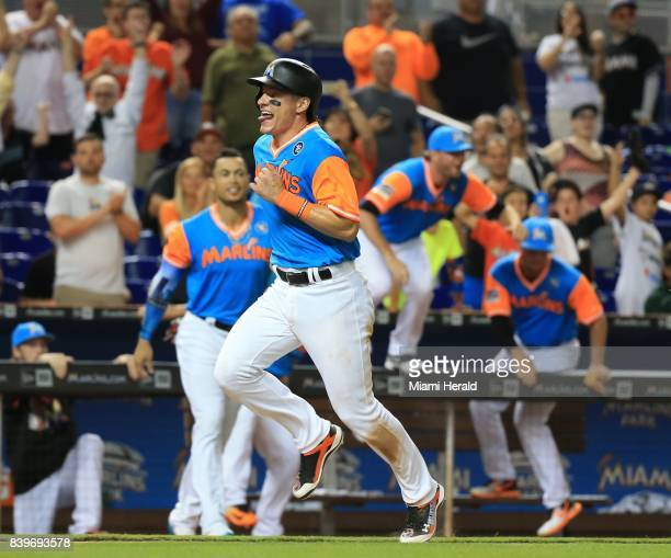The Miami Marlins' Derek Dietrich runs to home plate to score in the 11th inning on a sacrifice fly by Miguel Rojas against the San Diego Padres at...