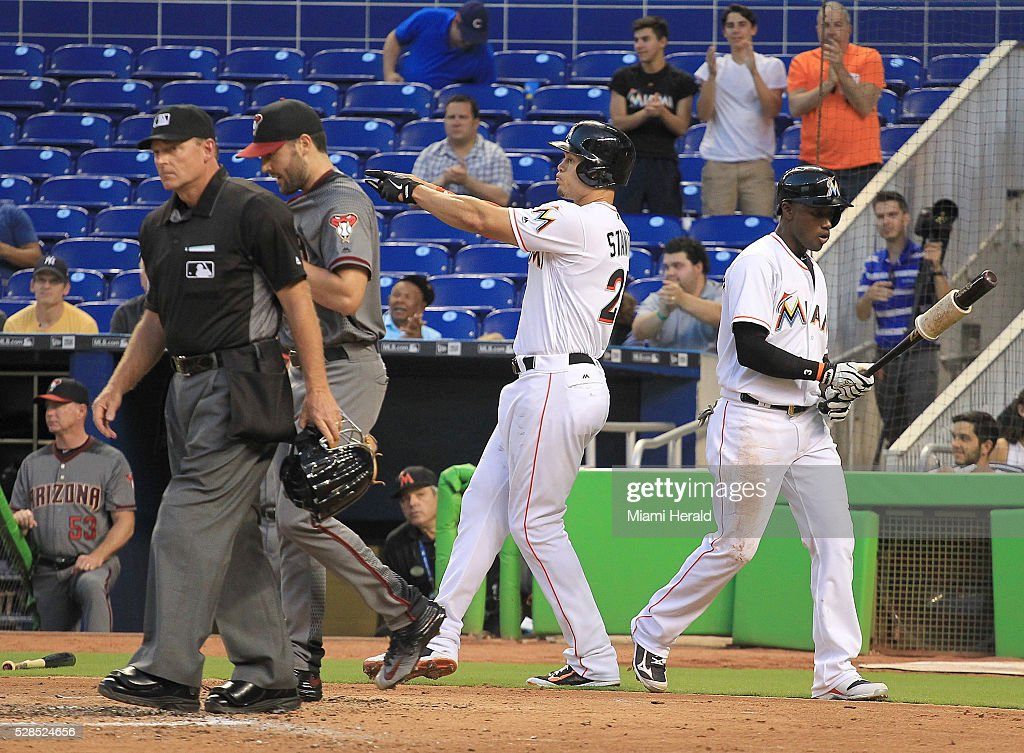 The Miami Marlins' Giancarlo Stanton, center, points to the Arizona Diamondbacks' dugout after scoring a run in the second inning at Marlins Park in Miami on Thursday, May 5, 2016.