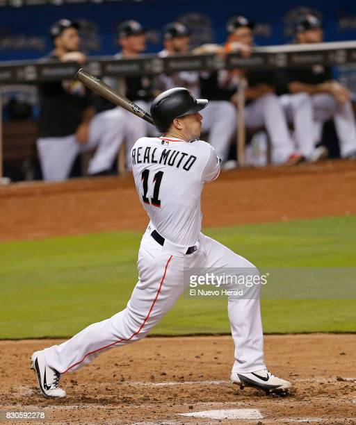 The Miami Marlins' JT Realmuto drives in a run with a sacrifice fly during the sixth inning against the Colorado Rockies at Marlins Park in Miami on...