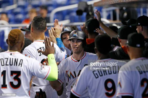 The Miami Marlins' JT Realmuto is congratulated by teammates after scoring a run during the first inning against the San Francisco Giants at Marlins...
