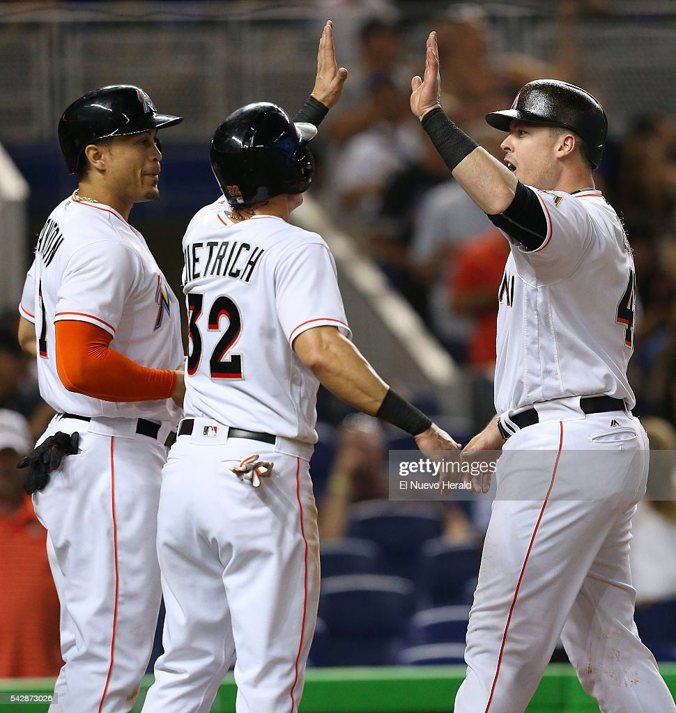 The Miami Marlins' Justin Bour, right, is congratulated by teammates Giancarlo Stanton and Derek Dietrich (32) after hitting a grand slam during the first inning against the Chicago Cubs on Friday, June 24, 2016, at Marlins Park in Miami.