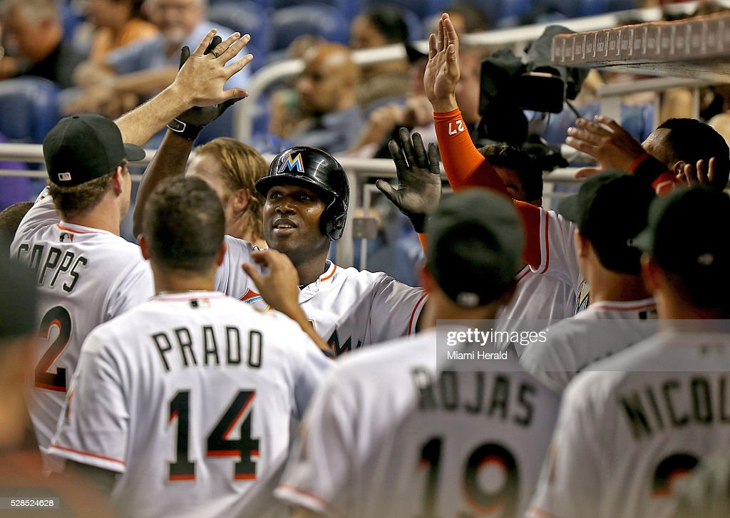 The Miami Marlins' Marcell Ozuna, center, gets high-fives in the dugout after scoring a run in the fourth inning against the Arizona Diamondbacks at Marlins Park in Miami on Thursday, May 5, 2016.