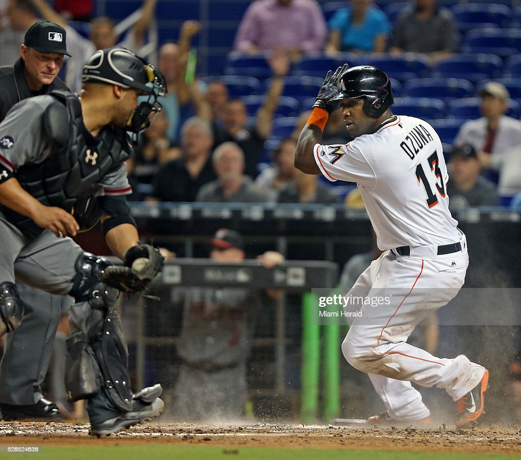 The Miami Marlins' Marcell Ozuna, right, avoids the tag from Arizona Diamondbacks catcher Welington Castillo as he scores in the fourth inning at Marlins Park in Miami on Thursday, May 5, 2016.