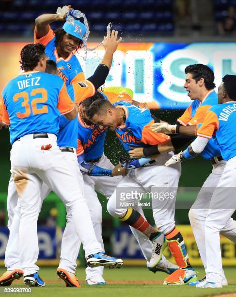 The Miami Marlins' Miguel Rojas is surrounded by teammates after hitting a gamewinning sacrifice fly in the 11th inning against the San Diego Padres...