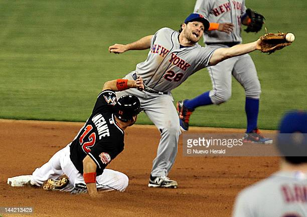 The Miami Marlins' Omar Infante steals second base as the New York Mets' Daniel Murphy stretches to get the ball during the first inning at Marlins...