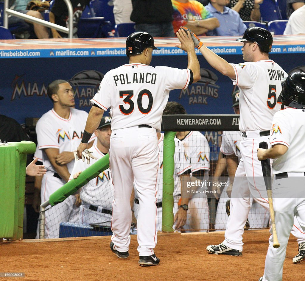 The Miami Marlins' Placido Polanco (30) high-fives teammate Jordan Brown after Polanco's RBI single in the fifth inning against the Philadelphia Phillies at Marlins Park in Miami, Florida, on Tuesday, May 21 2013.