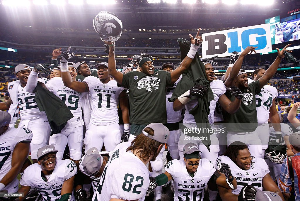 The Michigan State football team celebrates after beating the Iowa Hawkeyes in the Big Ten Championship at Lucas Oil Stadium on December 5 2015 in...