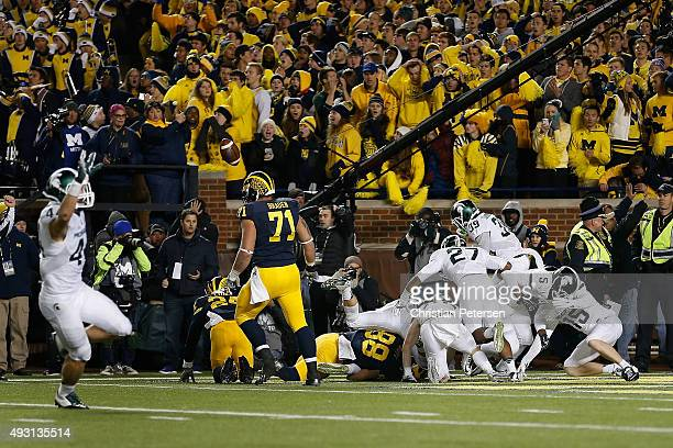 The Michigan State Spartans celebrate in the end zone after defensive back Jalen WattsJackson scored the game winning touchdown against the Michigan...