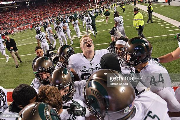 The Michigan State Spartans crowd around kicker Michael Geiger of the Michigan State Spartans to celebrate after Geiger's 41yard field goal defeated...
