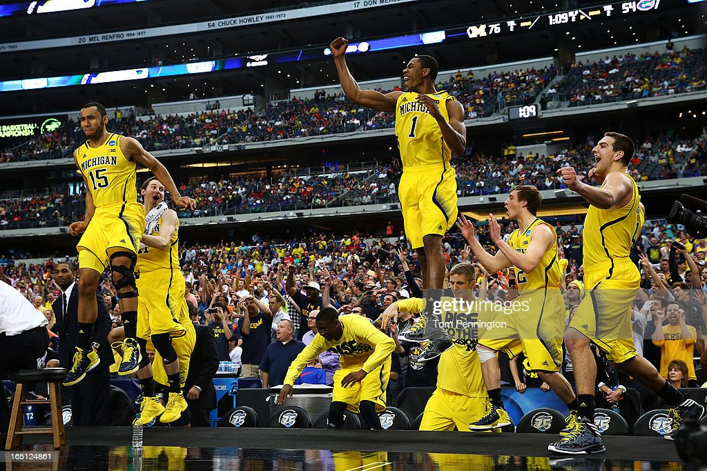 The Michigan Wolverines bench celebrates their 79 to 59 win over the Florida Gators during the South Regional Round Final of the 2013 NCAA Men's Basketball Tournament at Dallas Cowboys Stadium on March 31, 2013 in Arlington, Texas.