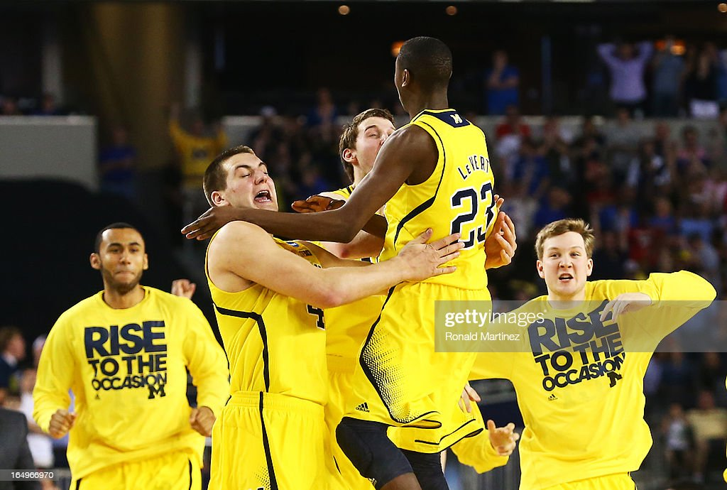 The Michigan Wolverines celebrate their 87 to 85 win over the Kansas Jayhawks in overtime during the South Regional Semifinal round of the 2013 NCAA Men's Basketball Tournament at Dallas Cowboys Stadium on March 29, 2013 in Arlington, Texas.