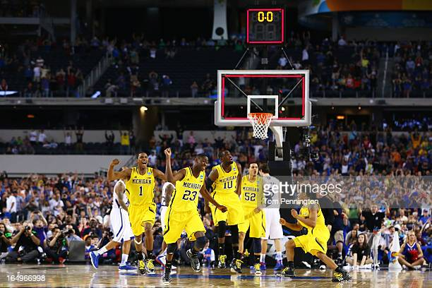 The Michigan Wolverines celebrate their 87 to 85 win over the Kansas Jayhawks in overtime during the South Regional Semifinal round of the 2013 NCAA...