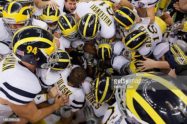 The Michigan Wolverines pile on kicker Brendan Gibbons after Gibbons kicked a successful 37yard gamewinning field goal in overtime against the...