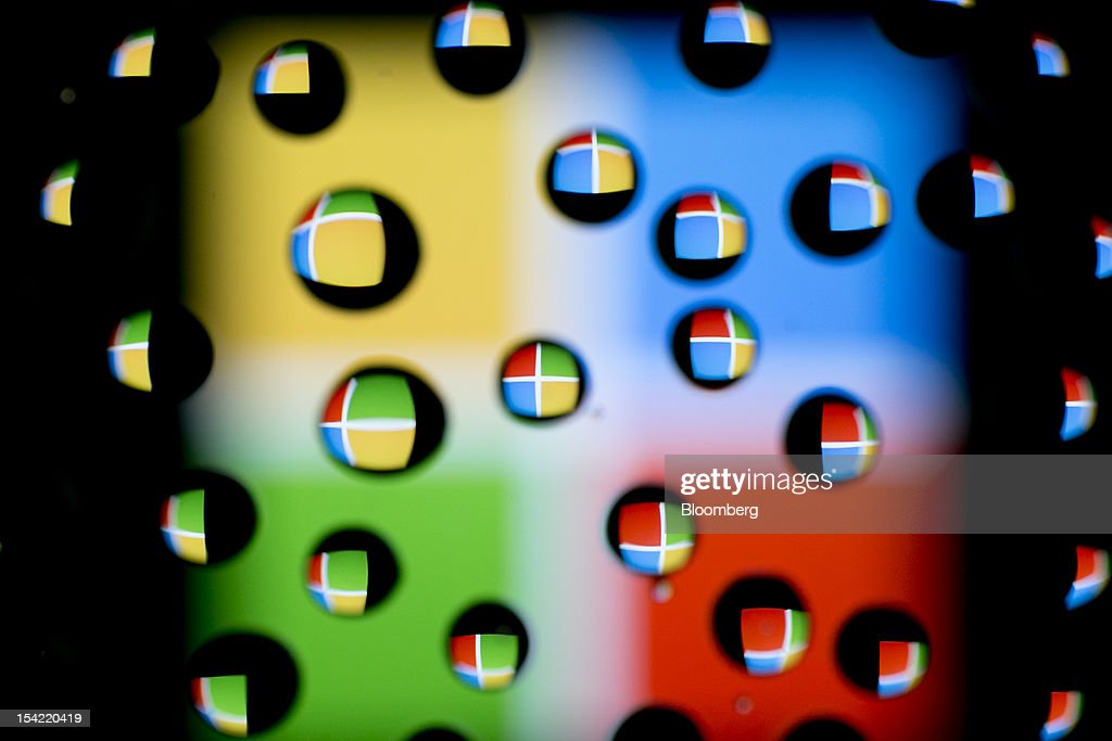 The Microsoft Corp. logo is reflected in water droplets for an arranged photograph in Washington, D.C., U.S., on Monday, Oct. 15, 2012. Microsoft Corp. is scheduled to release earnings data on Oct. 18. Photographer: Andrew Harrer/Bloomberg via Getty Images
